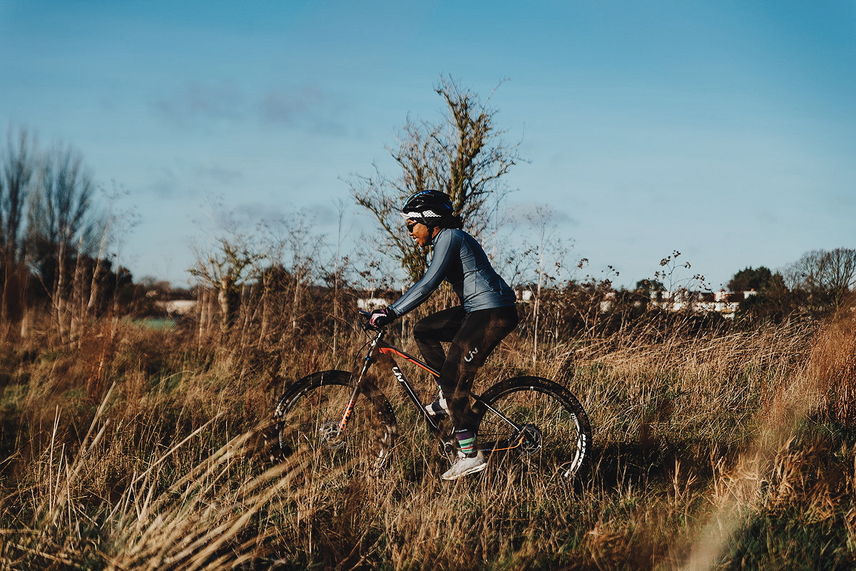 Elle on a mountain bike in a grassy area - How To Apply Chamois Cream For Female Cyclists