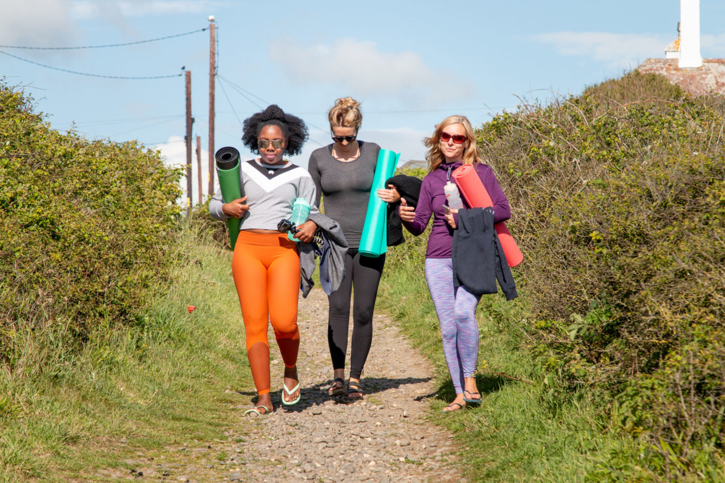 Three women walking along a dirt path towards the beach