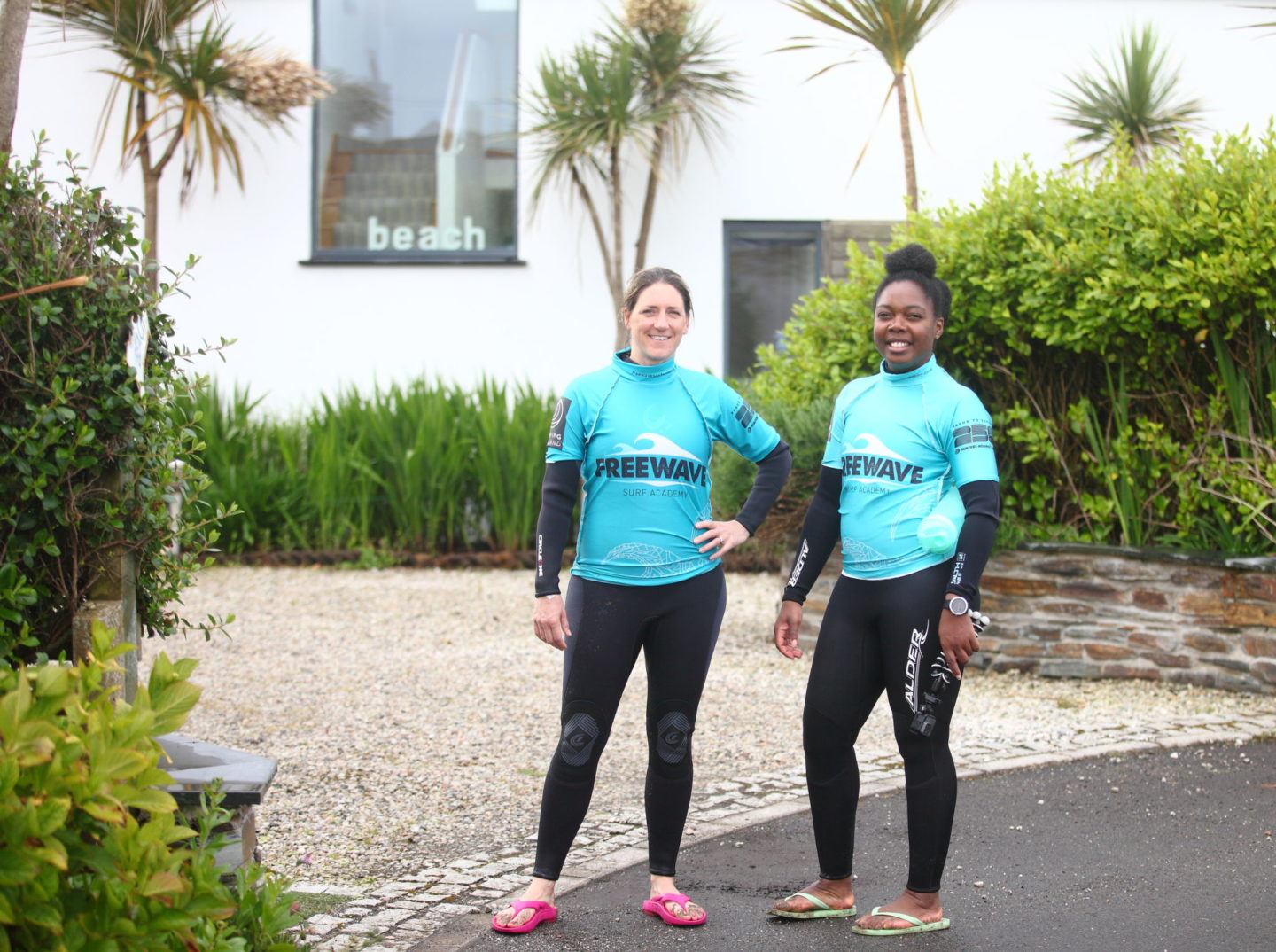 Two surfers standing at the end of the drive of the house where a fitness retreat is being hosted