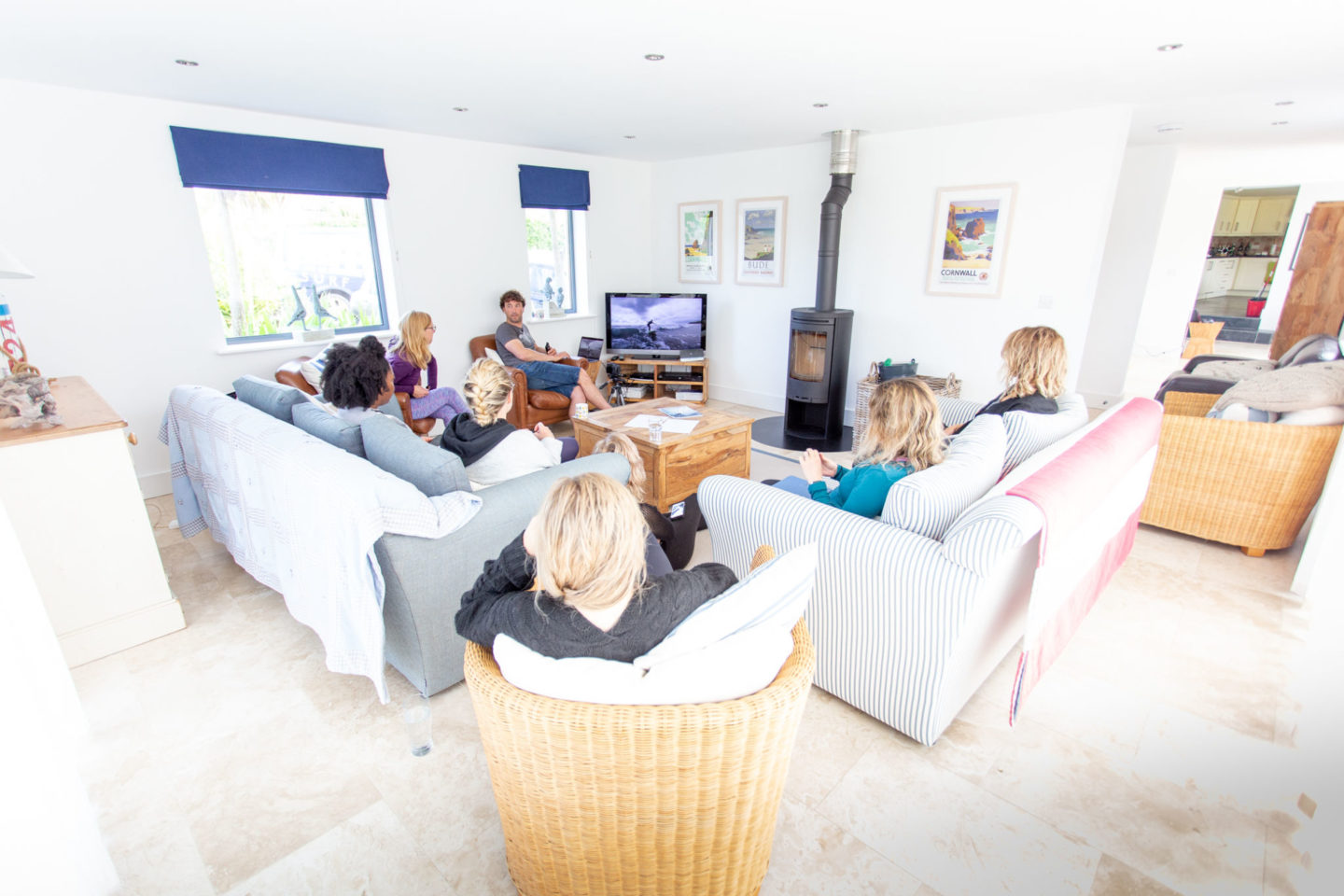 group of people sat on sofas in a living room looking at feedback from a surf lesson on the tv