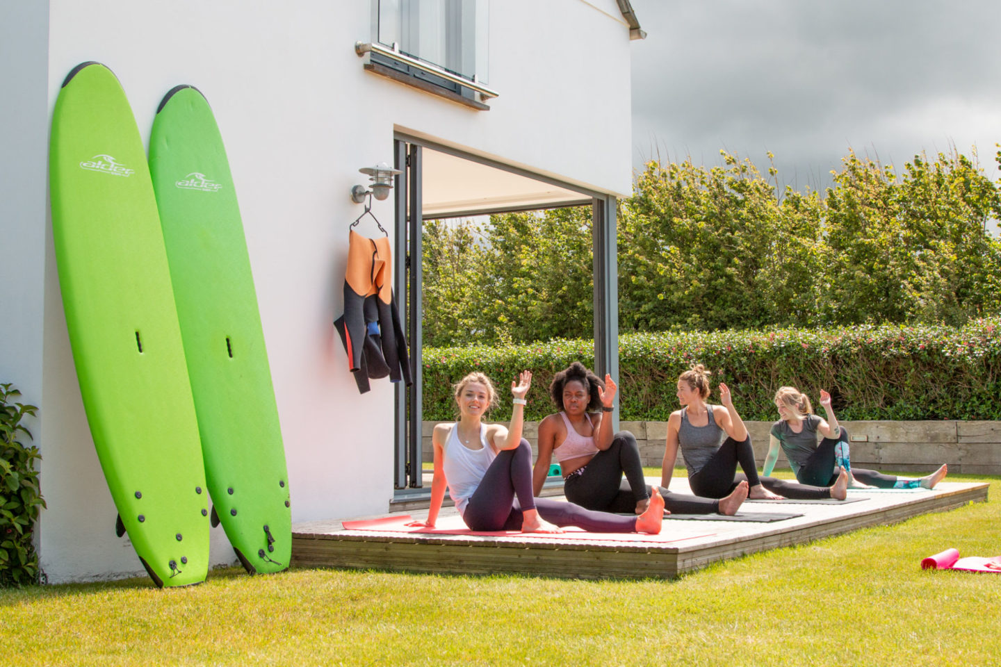 Freewave surf academy hosting a yoga class on their fitness retreat in the garden of a house