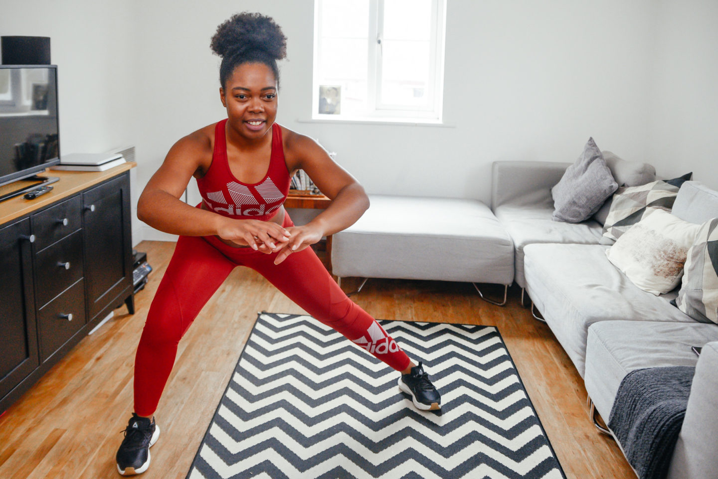 How To Stay Fit By Working Out From Home - Elle in a side lunge position
