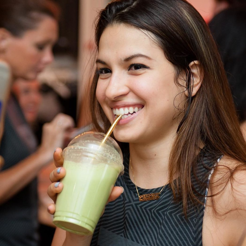Girl smiling while drinking green smoothie from gold straw