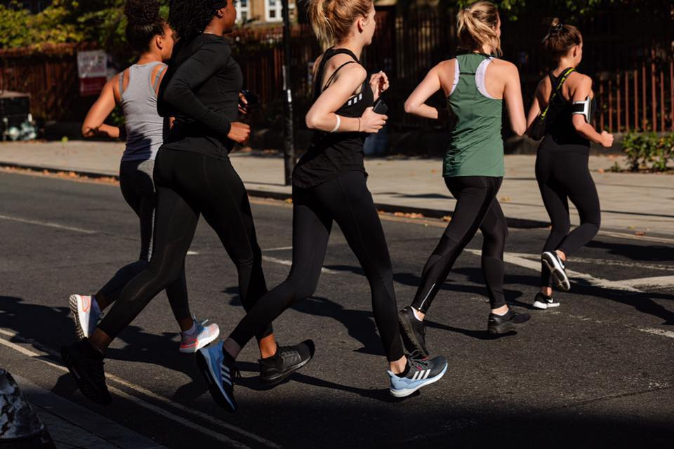 five female runners, running across the road - dealing with shin splints