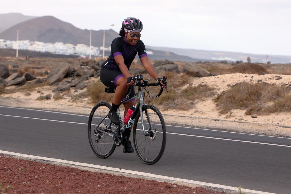 Elle on her bike, smiling during the bike leg of CLS mini triathlon.