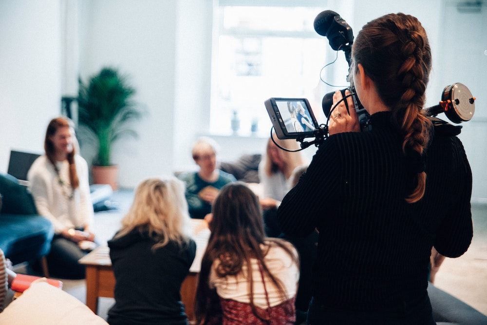 Woman holding a camera whilst filming a workshop - Tips For Planning & Editing Your Fitness Videos