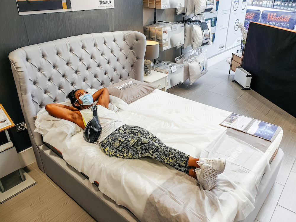 Elle laying on a bed and mattress in the TEMPUR®  Westfield Stratford