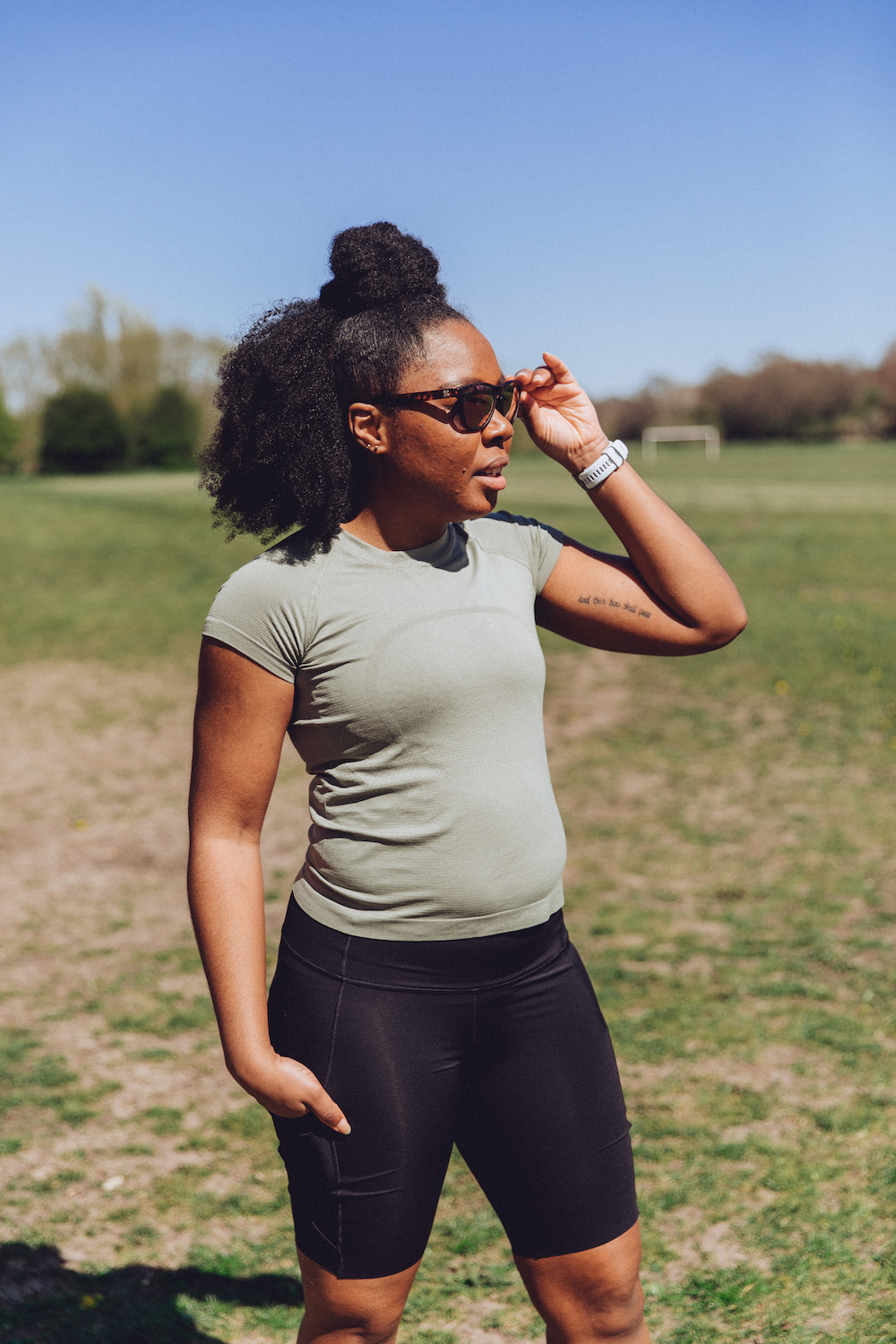 Elle wearing lululemon running top and lululemon running shorts looking into distance to the right while holding sunglasses with left hand