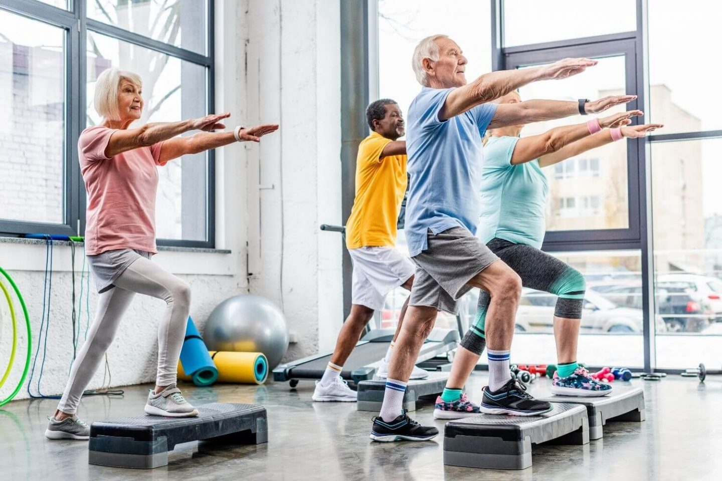 4 older individuals partaking in a step exercise class with hands raised in front of them as they step their right feet onto the step.
